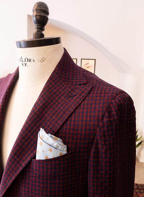 Zoom su manichino con giacca estiva quadretti blu e rossi con fazzoletto in cotone celeste nel taschino