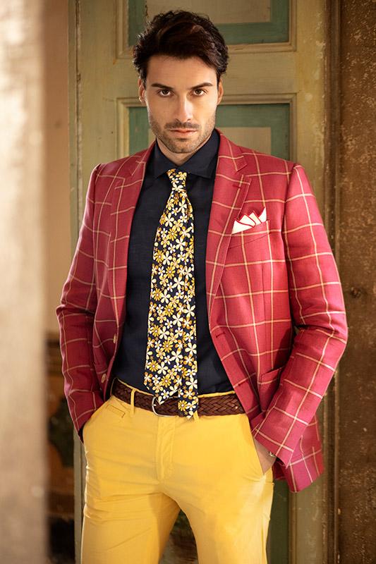 Modello con giacca quadri corallo, pantaloni cotone, camicia blu scuro e cravatta a fiori disegno vintage