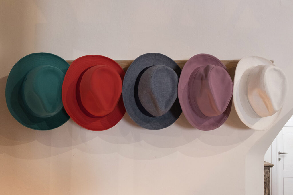 Serie di cappelli estivi colorati appesi su appendiabiti in showroom