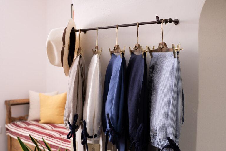 Pantalacci in lino diversi colori appesi in showroom con sfondo cassapanca antica