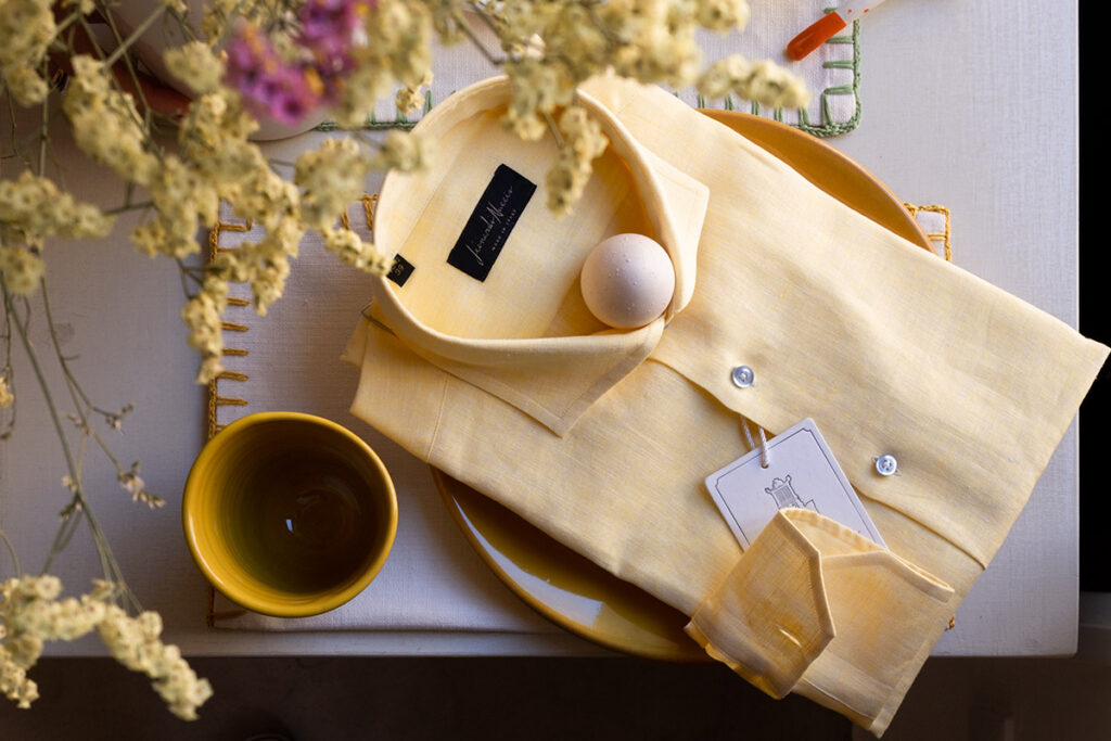 Quadro estivo con camicia in lino gialla, ceramiche senape salentine e fiori