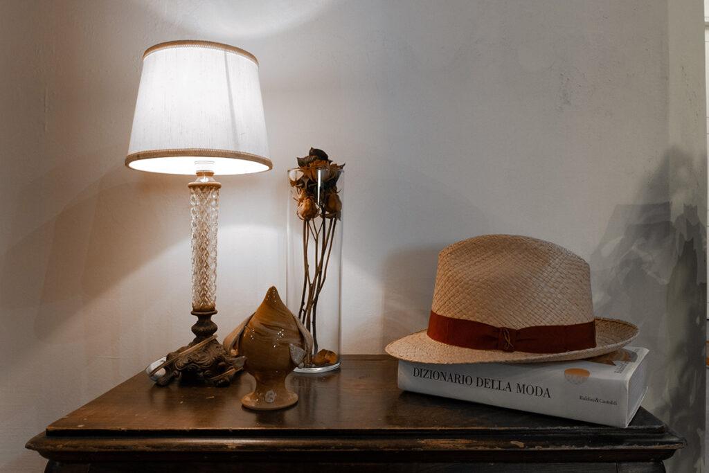 Piccolo mobile antico con paralume vintage, pumo pugliese in ceramiche, vaso con rose secche e cappello Doria in paglia