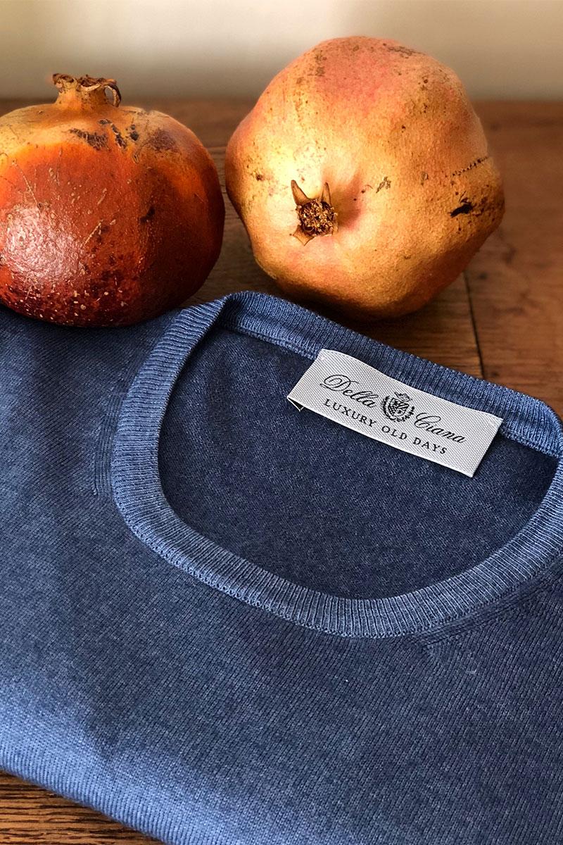 Dettaglio girocollo merinos blu su tavolo antico e frutta autunnale
