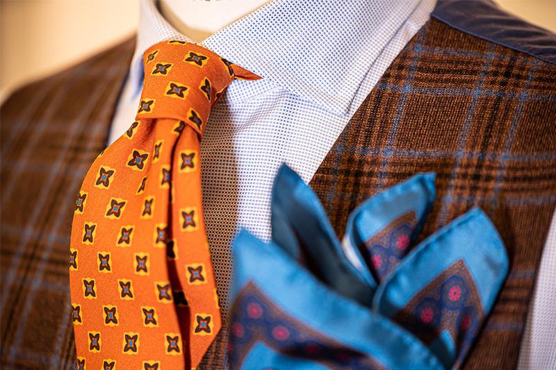 Outfit cravatta arancione seta, camicia cotone micro disegni celeste e gilet Principe di Galles marrone