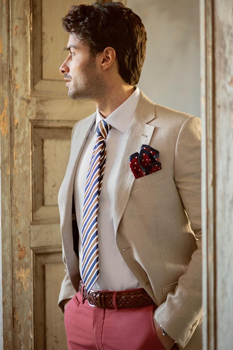Outfit giacca lino beige, camicia bianca, cravatta righe blu e senape, pantaloni cotone rosso scuro e cintura intrecciata in pelle