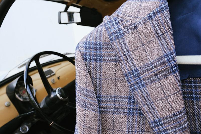 Dettaglio rever giacca estiva Principe di Galles marrone e blu con sfondo fiat 500 d'epoca