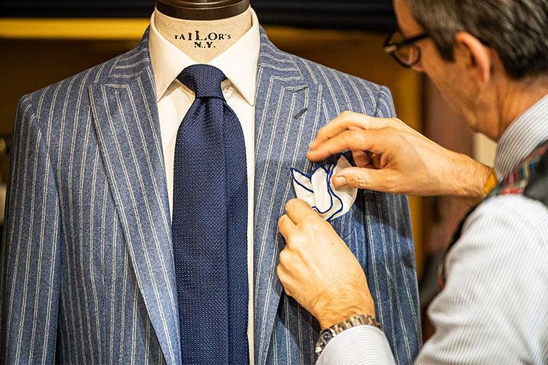 Leonardo Nuccio con outfit giacca lana celeste e bianca righe, camicia bianca e cravatta garza di seta blu