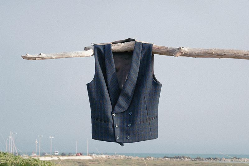 Gilet lana Principe di Galles blu doppiopetto sciallato appeso a ramo secco con sfondo mare Salento