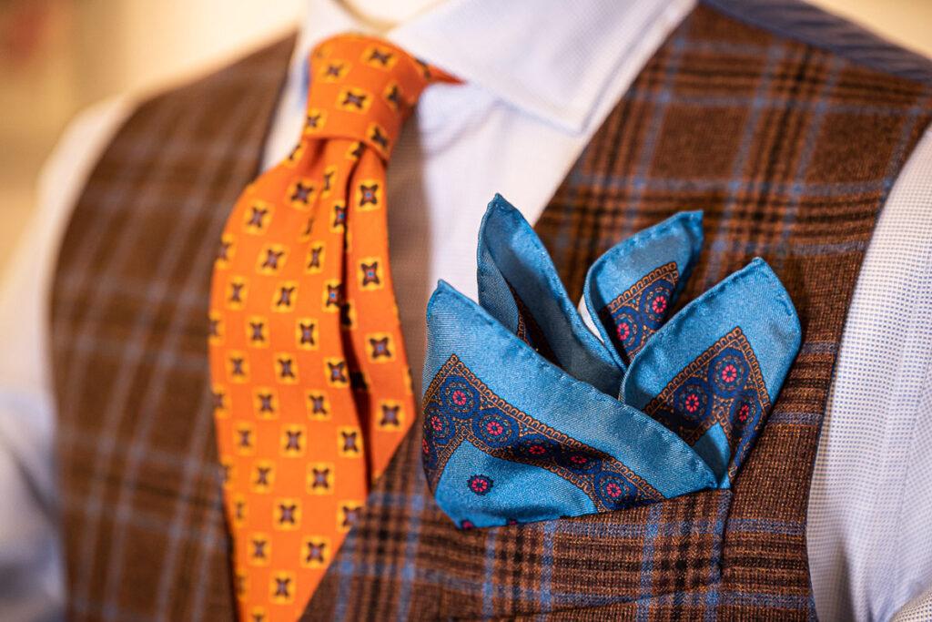 Dettaglio outfit invernale con gilet Principe di Galles marrone e azzurro, cravatta arancione e fazzoletto azzurro disegno cachemire in seta