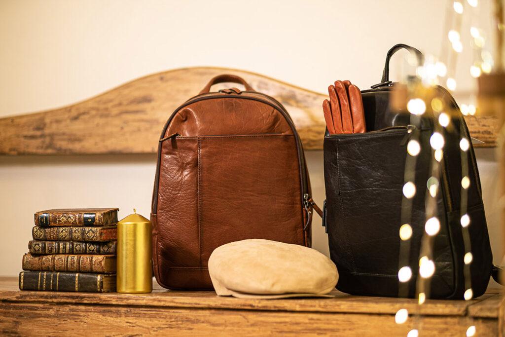 Composizione regali natalizia con libri antichi, candela dorata, due zaini in pelle uomo, coppola beige e guanti in pelle