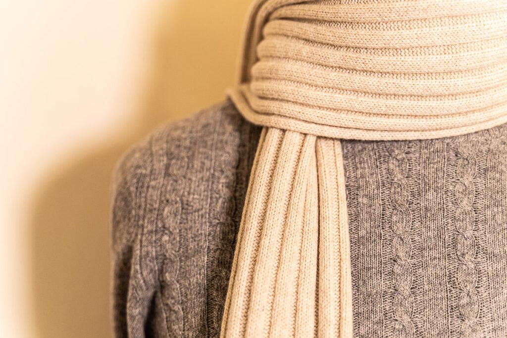 Zoom sciarpa a coste in lana panna e girocollo in lana a trecce grigio