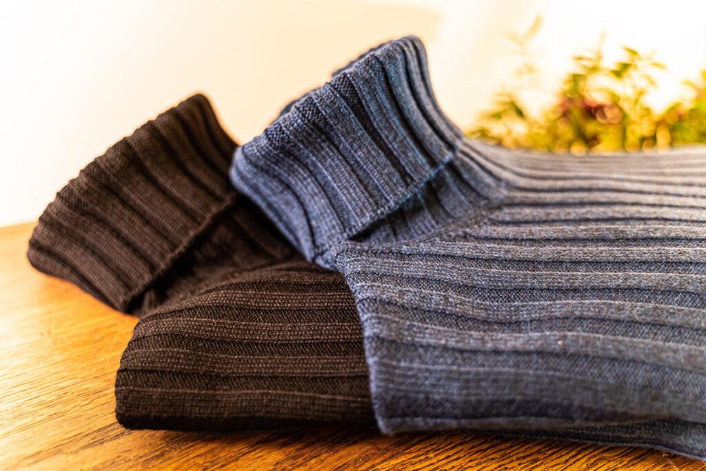 Maglioni dolcevita a coste in lana merinos nero e blu oceano piegati su tavolo antico
