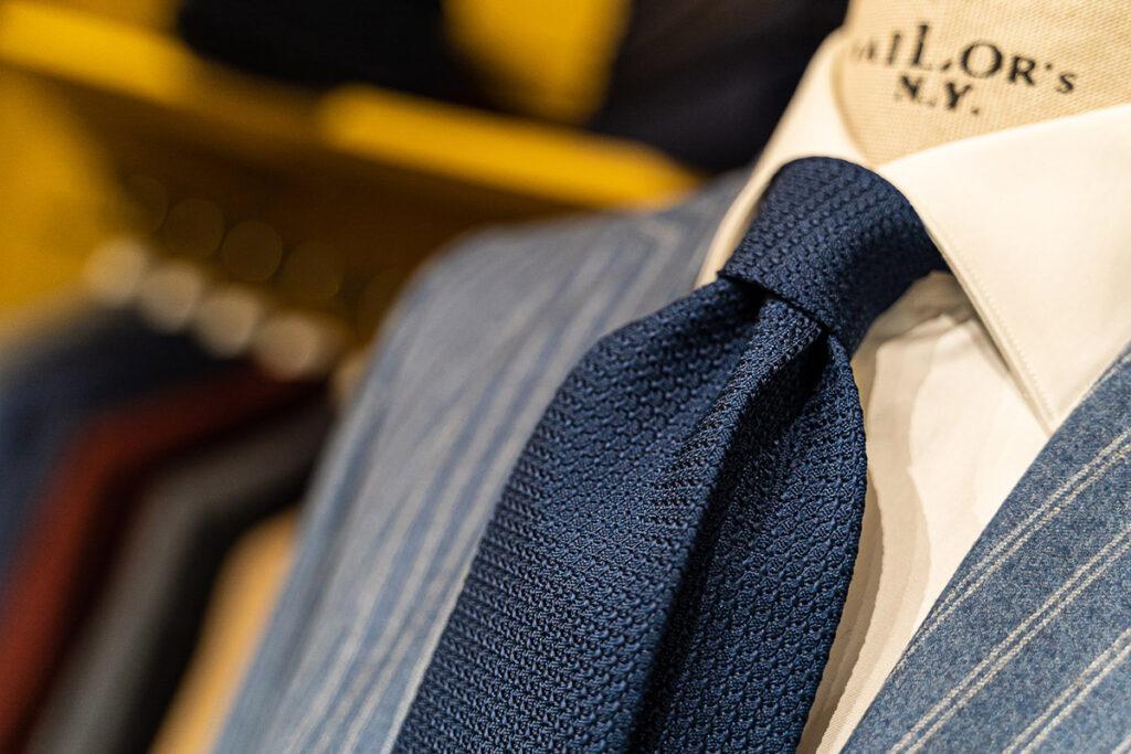 Zoom su outfit invernale con giacca celeste in flanella a righe bianche, cravatta in seta di garza blu e camicia bianca