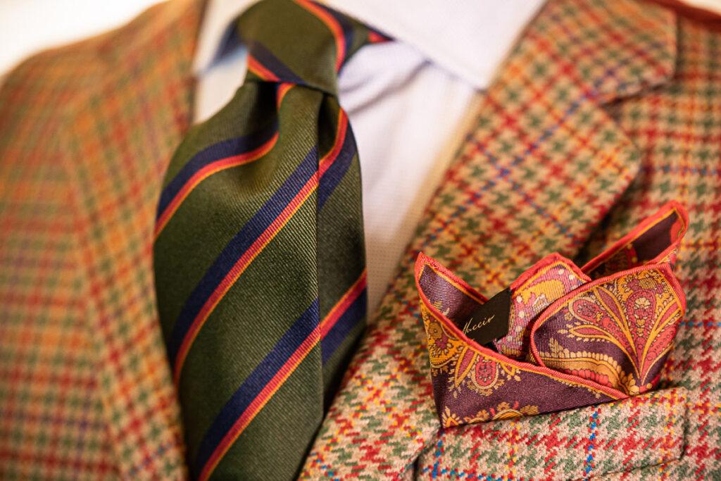 Zoom su outfit invernale con gilet pied-de-poule beige, verde e rosso, cravatta in seta regimental e fazzoletto in seta disegno cachemire