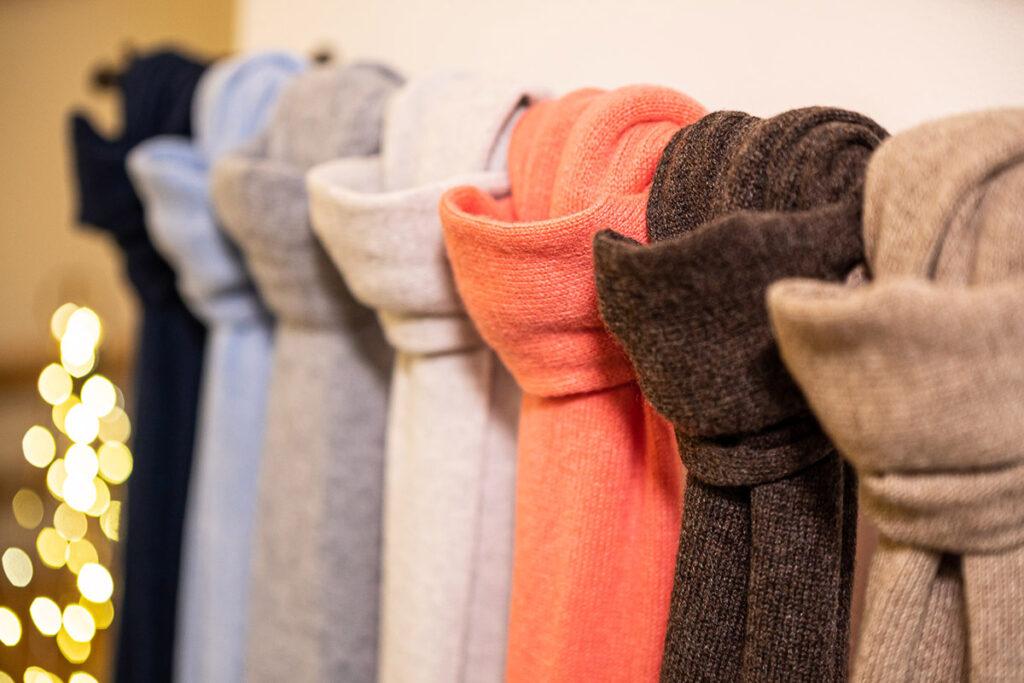 Sciarpe appese in puro cashmere diversi colori con atmosfera natalizia