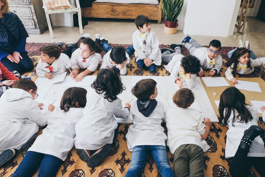 Bambini su tappeto intenti a disegnare le loro cartoline per la festa del papà
