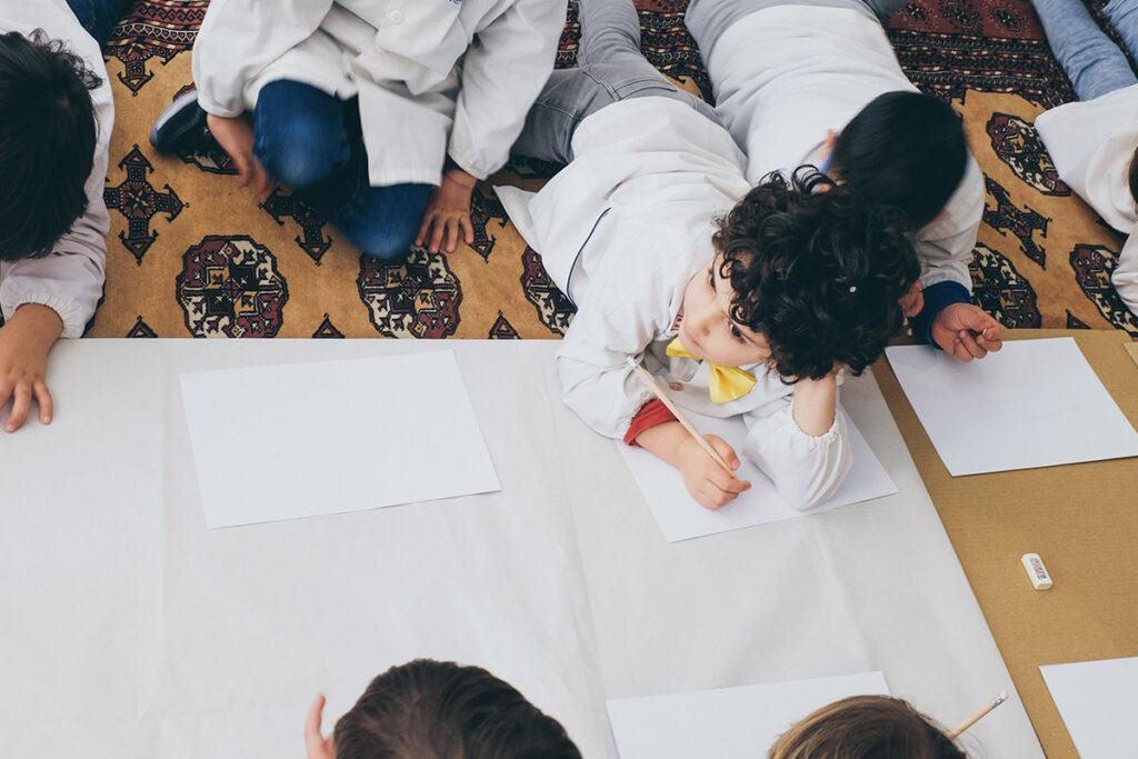 Bambino steso su tappeto mentre disegna per la festa del papà