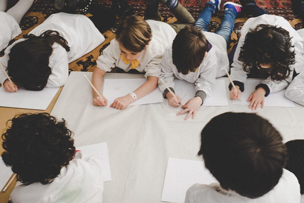 Bambini stesi su tappeto mentre disegnano cartolina per la festa del papà