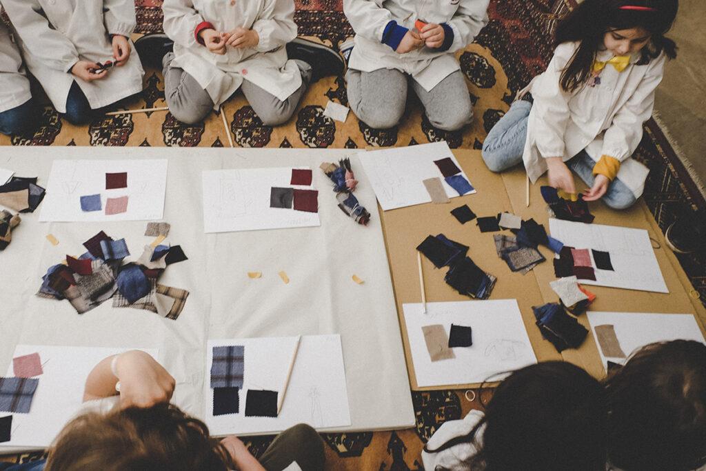Bambini stesi su tappeto mentre scelgono tessuti da abbinare al loro disegno per la festa del papà