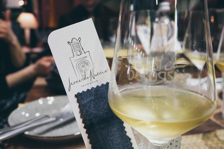 Calice di vino bianco Conti Zecca accanto a segnalibro Leonardo Nuccio Showroom personalizzato con tessuto