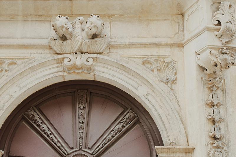 Dettaglio teste di angelo su arcata portone palazzo barocco Tricase